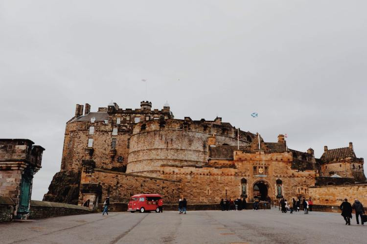 View of Edinburgh Castle from the Royal Mile. The image is in thirds, with the grey pavement in the bottom third, the castle is brown with turrets and a Scottish flag and in the top third is a grey sky. A small red van selling ice cream to tourists is at the left side.