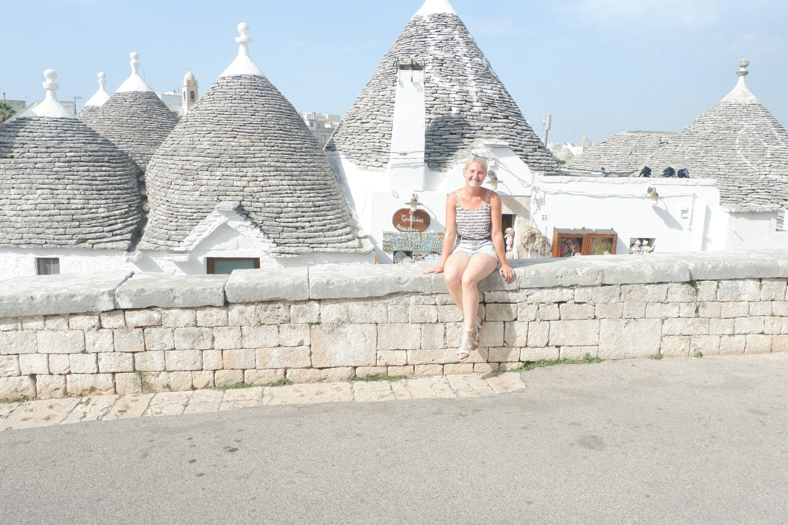 Emily sitting on a wall in front of Trulli in Alberobello