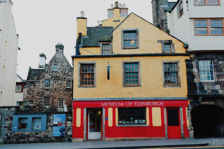 The exterior of the Museum of Edinburgh, from across the road. The top half of the building is two stories with yellow paint. The lower half is red with the name Museum of Edinburgh in white.
