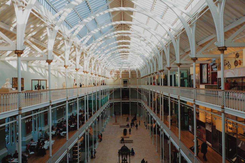 View over the main gallery of the National Museum of Scotland, from the top floor, looking over the three levels. The gallery has a glass roof and white posts around each of the balconies.