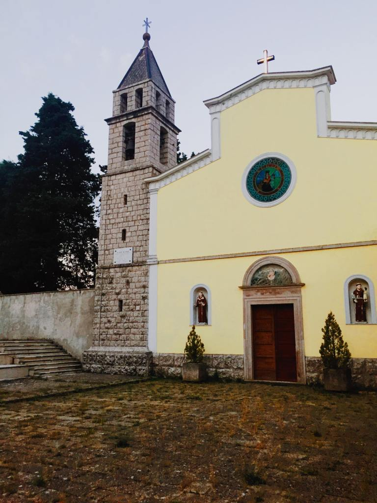 The convent of Santa Maria Delle Grazie in Jelsi, which is yellow with statues either side of a door and a circular stain glass window and cross on the top.