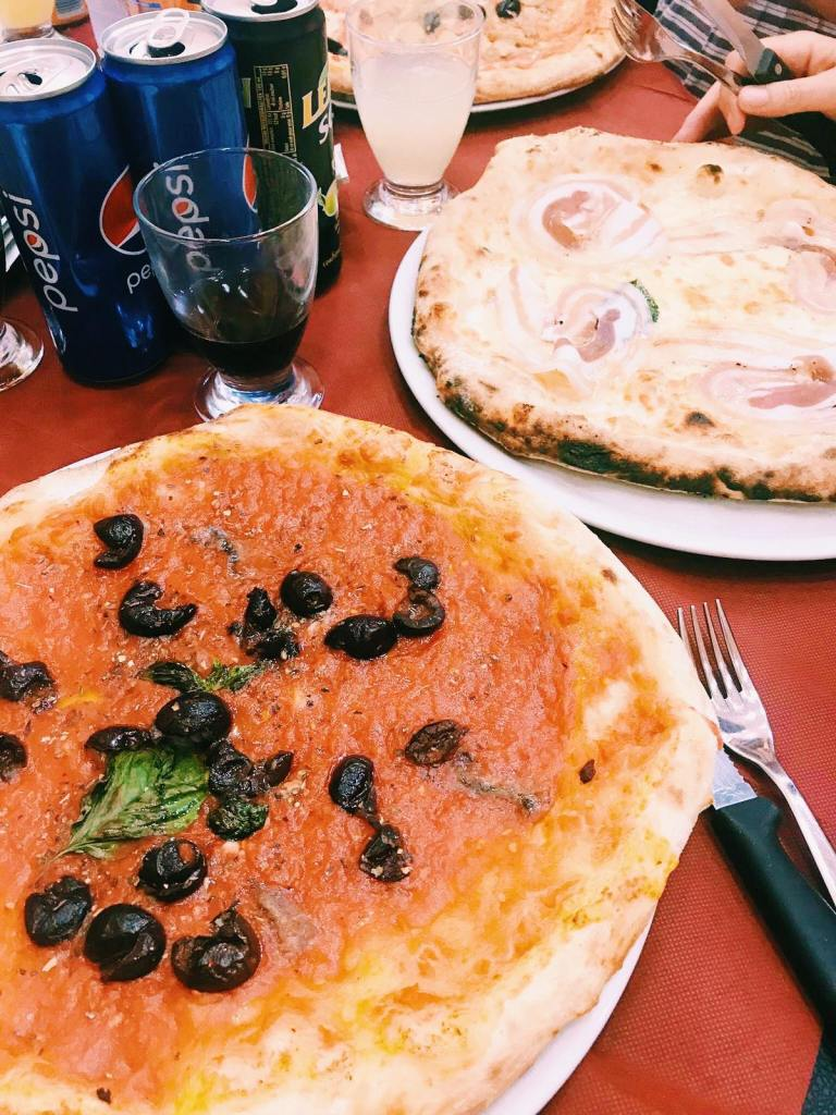 Marinara Pizza on a plate with black olives and basil, behind is a pizza with cotta and some Pepsi cans