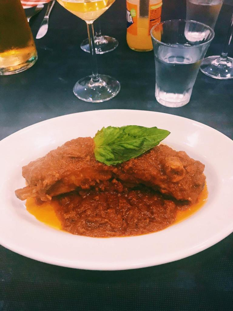 A rib on a white plate with the Naples Ragu sauce over it, and a basil leaf on top.