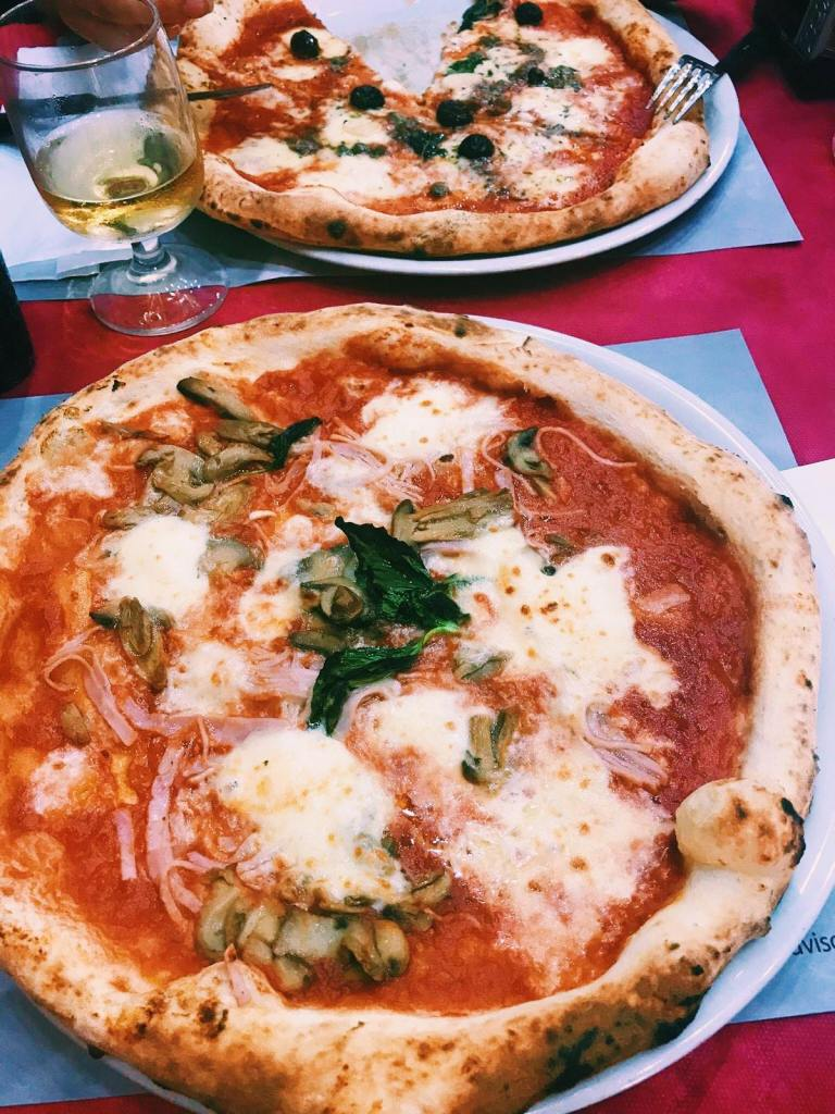 A large pizza with mozzarella, basil, shredded ham and mushrooms. Behind is a pizza with a slice cut out, with black olives and capers on it. A wine glass with white wine in between the Neapolitan pizza