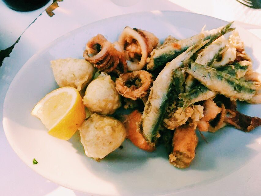 Plate of Naples fried fish, sardines, octopus and squid with a lemon slice
