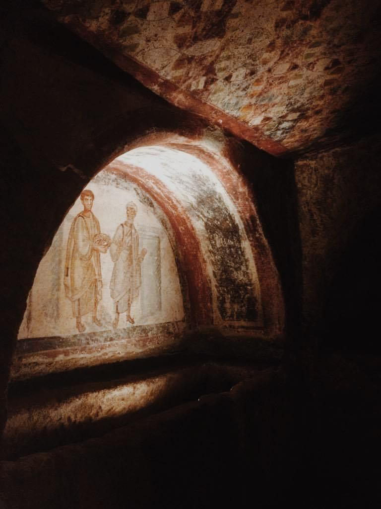 Fresco in an alcove in the San Gennaro catacombs of two men in robes.