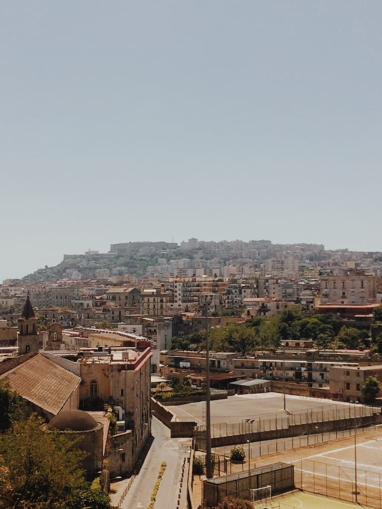 View of Naples, Italy from Cappodimonte, at the entrance to San Gennaro Catacombs. Image is filled with brown and yellow buildings up a hill.