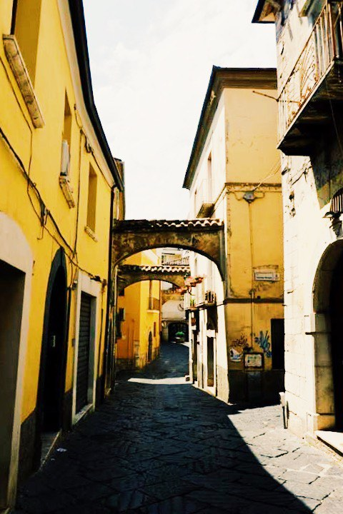 Street in Benevento Campania. With yellow buildings either side and arches between buildings.