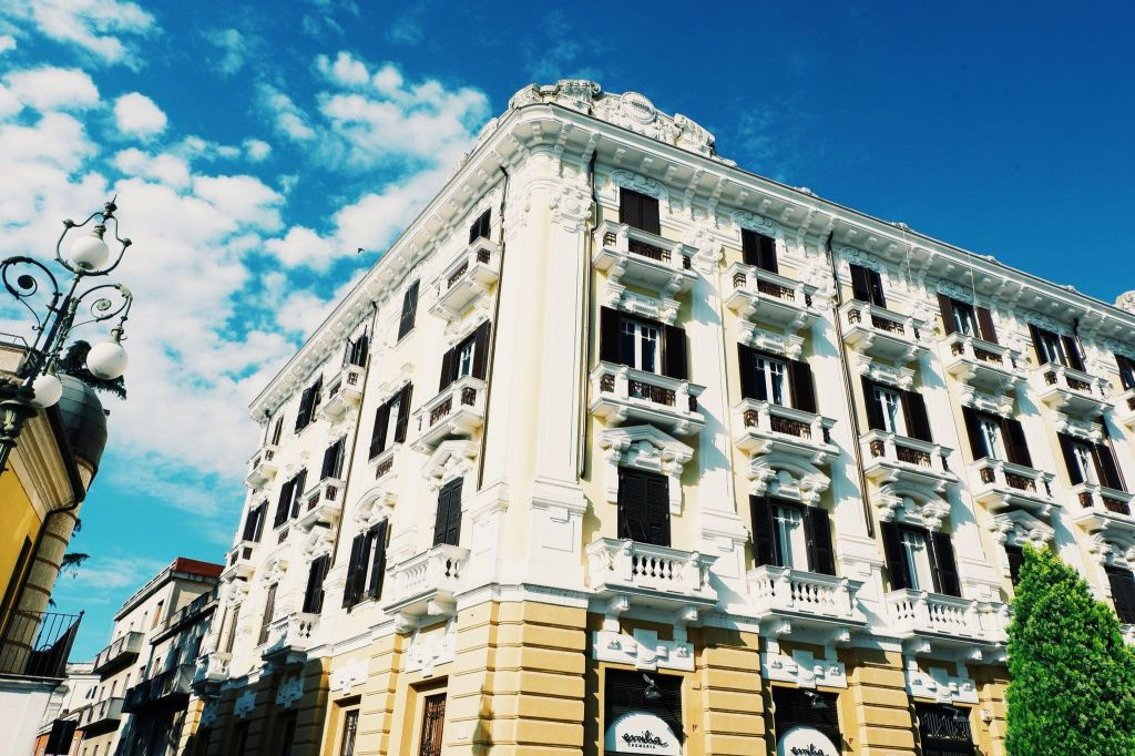 Things to see in Benevento, Campania. Corner of a large building with 4 floors, top three floors are yellow and white. Windows with balconies and wooden shutters