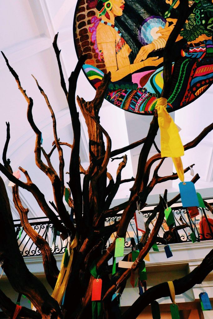 Tree in the centre of the World Gallery in the Horniman Museum with colourful ties and notes hanging off the wooden branches.