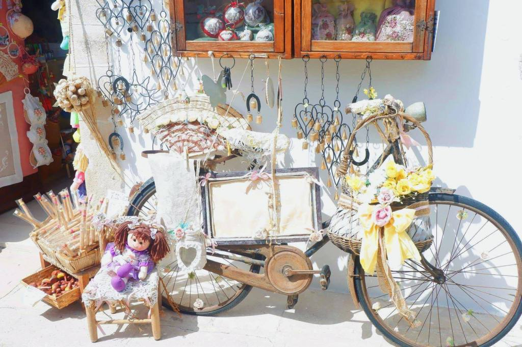 A bike with trinkets and gifts hanging off of it. It is surrounded by wind chimes in the shape of hearts and suns. There is a window with Christmas decorations in it. A purple doll sits in a small chair in front of the bike. It is a gift shop in a trulli in Alberobello.