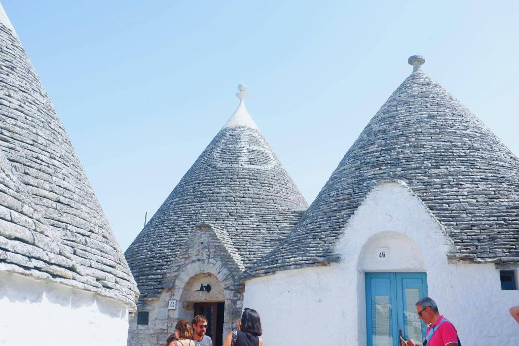 Stone rooms of Trulli in Alberobello. Three trulli are beside one another, the middle one has a white painted symbol and a pinnacle on top.
