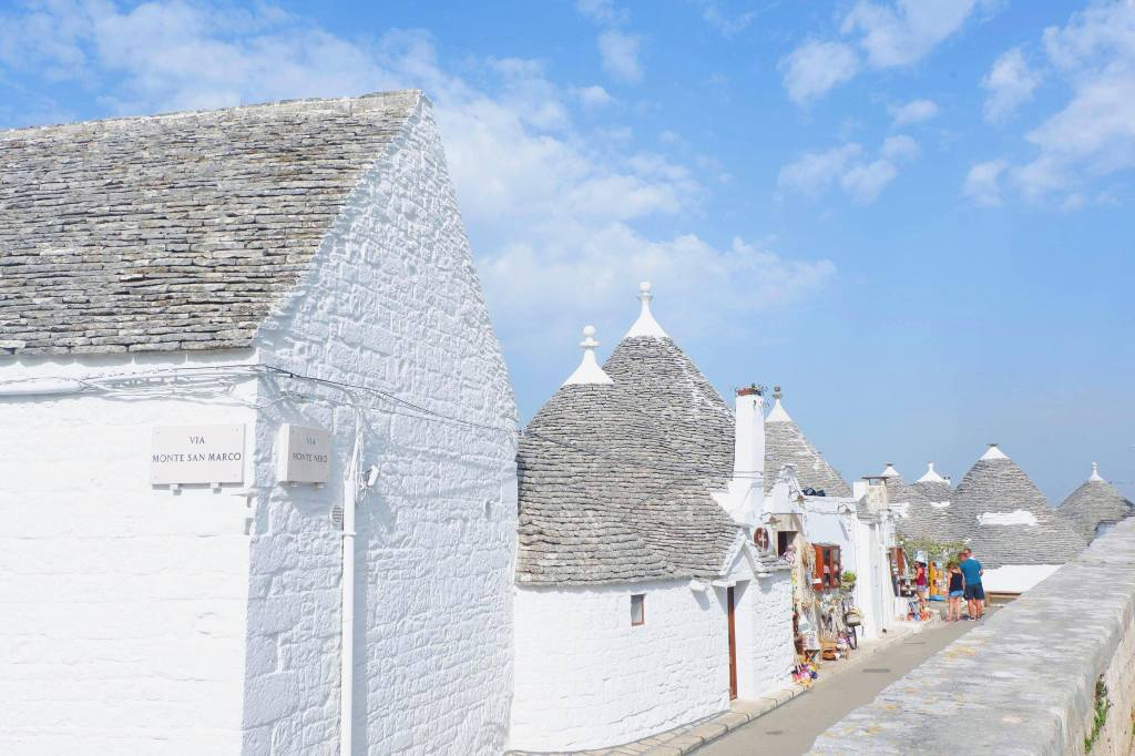 A row of trulli in Alberobello, along the left hand side are 6 trulli and along the right hand side is a wall. Some tourist are at the back of the path looking at souvenirs in a shop.