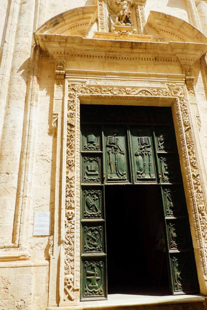 The door of the cheese di Santa Maria, in Monopoli Puglia. The iron door has skeletons on it and the stone around the door is carved with skulls and cross bones.