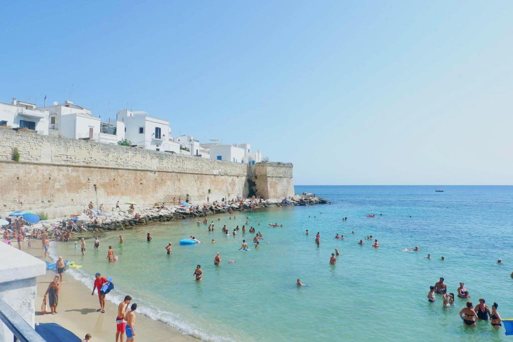 The beach in Monopoli, Puglia. The sky is blue, the sea is a deep blue / green. A tall sandstone wall runs from the left to centre of the image. Tourists are in the water swimming and on the small area of sand.
