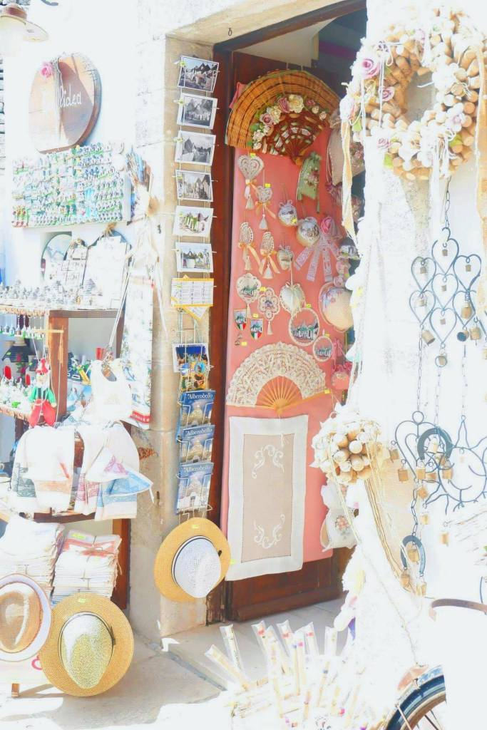 A door of a trulli in Alberobello. the doorway and walls are filled with souvenirs and gifts and post cards.
