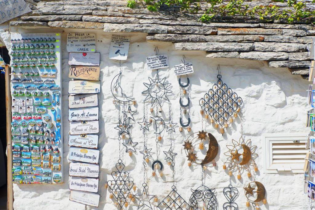 A gift shop in a trulli in Alberobello. Blue magnets hang down the left hand side, beside are house signs along, along most of the wall are wind chimes in the shape of moon, sun, stars, hearts.