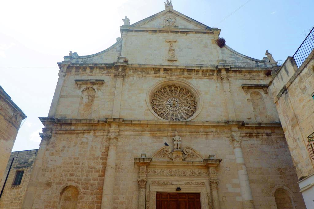 Church in Monopoli, Puglia. The church is three stories tall. The wooden door is centre. Above it is a large circular stained glass window. On either side is alcoves.