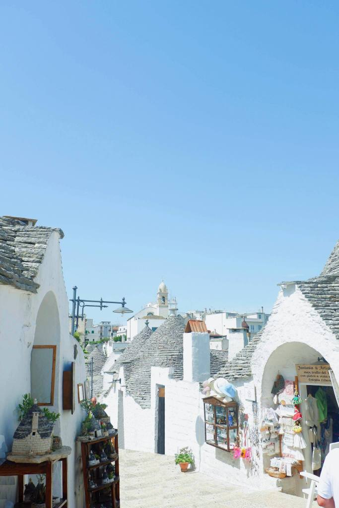 A street in Alberobello, line with Trulli. A white path is between the two rows of trulli, and many have gifts in their doors. Above the stone roofs and chimneys is a blue sky.