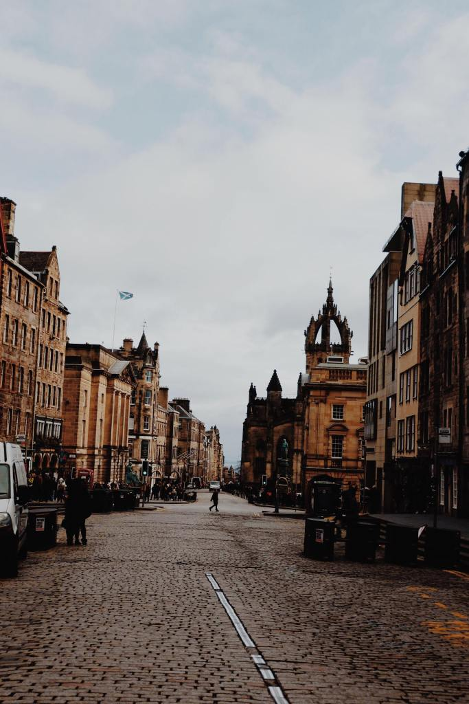 View of the Royal Mile from Castle hill. Brown buildings are either side of a cobbled road. A small Scottish flag on the left. On the right, the spire of St Giles Cathedral.
