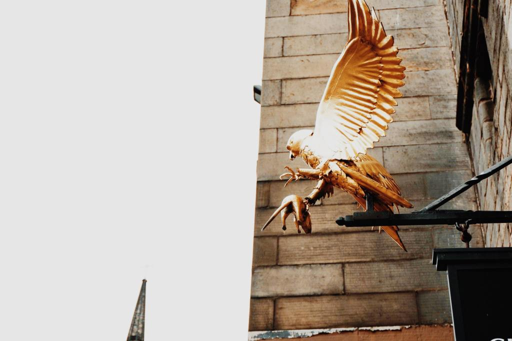 The golden flacon holding a mouse above the door of Gladstones Land on The Royal Mile Edinburgh