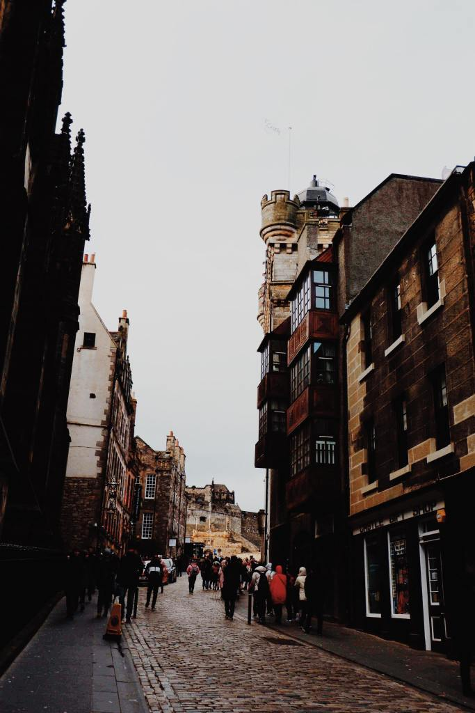 View of the Royal Mile, Edinburgh, Castlehill. Either side of the cobbled street are all brown buildings. At the centre back of the image is Edinburgh Castle.