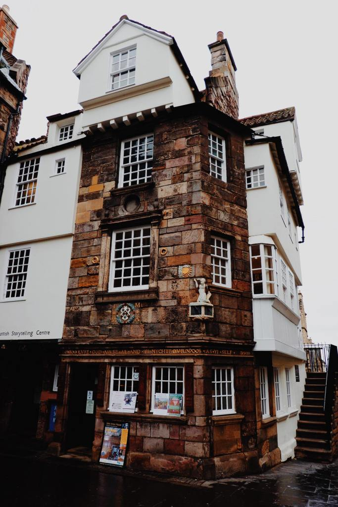John Knox house, with a mix of white facade and brown brick. There are 8 windows made up of smaller squares. On the ground floor is the entrance to the museum with signs up, and an outer staircase.