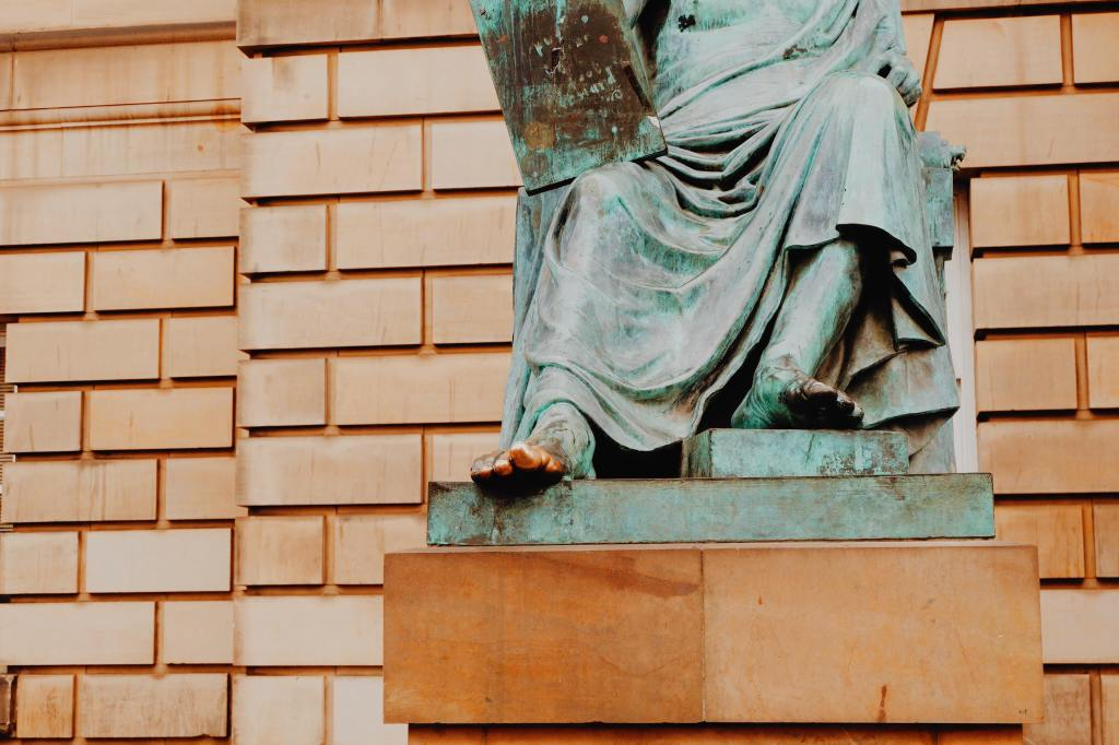 The statue of David Hume, which is green. The image is cropped at his waste and his golden toe is centre of the image.