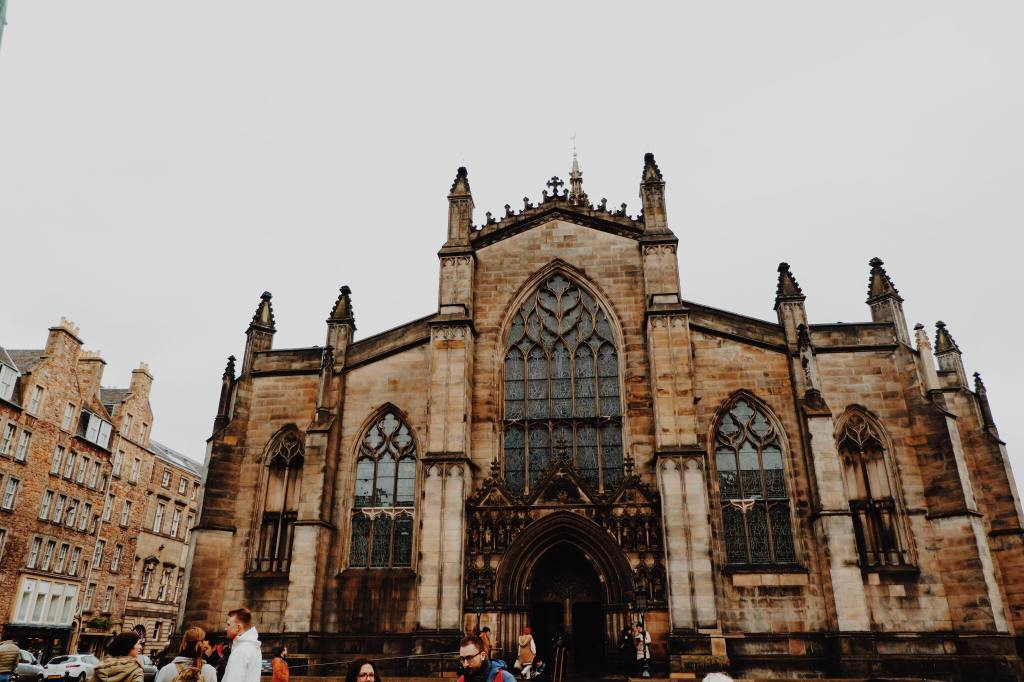 St Giles Cathedral on The Royal Mile. Three stained glass windows and an arched door way with elaborate carvings.
