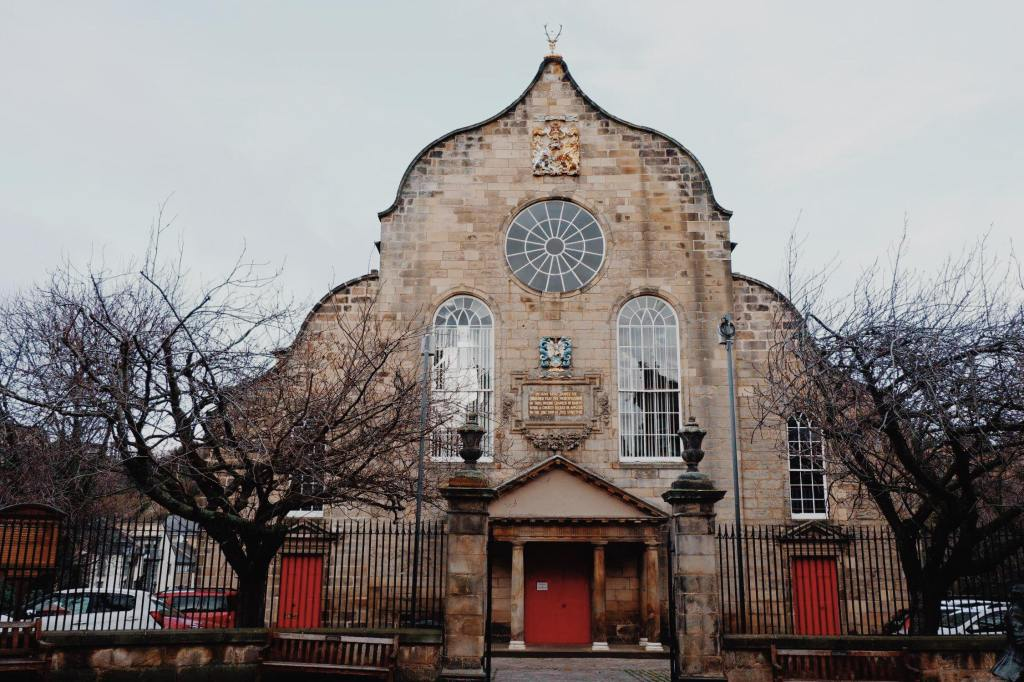 The Canongate Kirk on the Royal Mile Edinburgh. The building is tall with curved sides. At either side are brown trees in the winter. The is a red double door in the centre and two red doors either side. There are two tall windows and above one circular window.