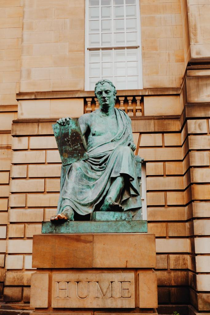 Statue of David Hume on the Royal Mile. The green statue of Hume sitting in robes holding a sign. His toe is gold. The statue sits on a carved stone saying HUME.