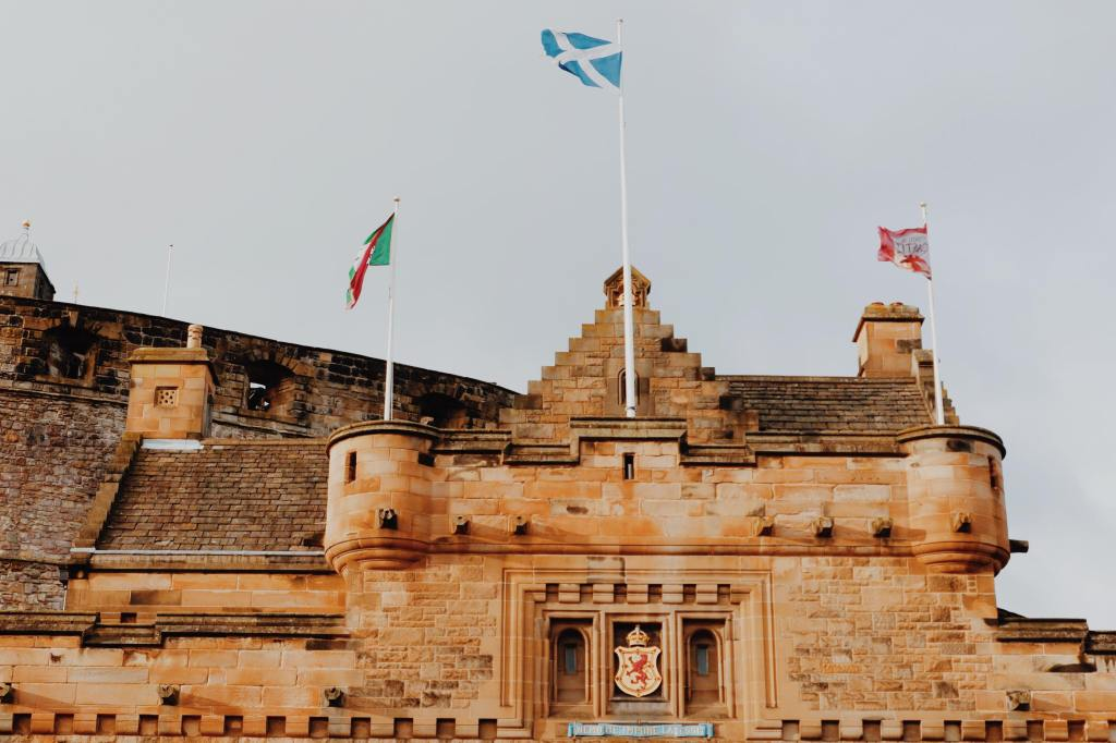 The Entrance to Edinburgh Castle with turrets. Three flags can be seen about the coat of arms. The Scottish flag in the middle. Edinburgh castle flag on the right and a green flag on left.