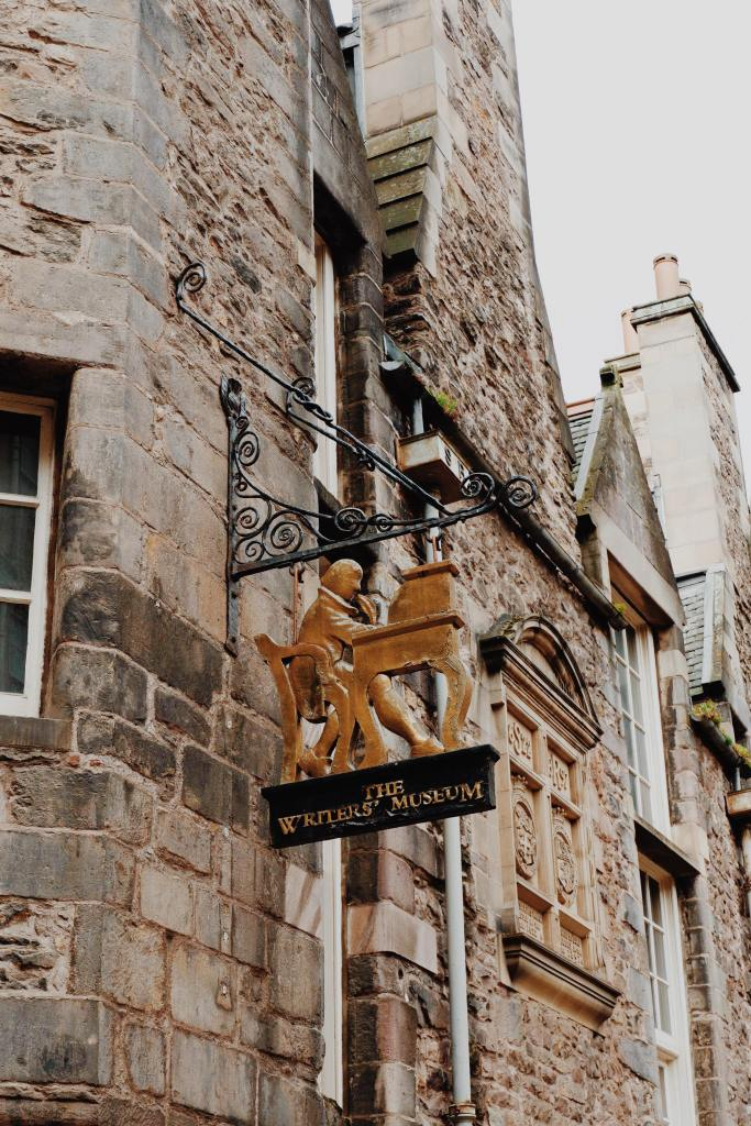 """The Gold sign of the writers museum which shows a writer at a desk with a feather quill. Underneath is a black plaque with gold letter """"The Writers' Museum"""""""
