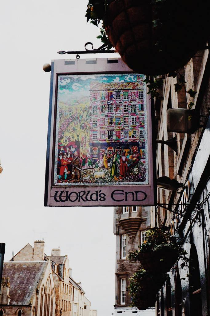 The colourful sign for The Worlds End pub, hanging on the right hand side of the buildings. The sign is mostly pink with an image of pub and a busy street in medieval style of painting.