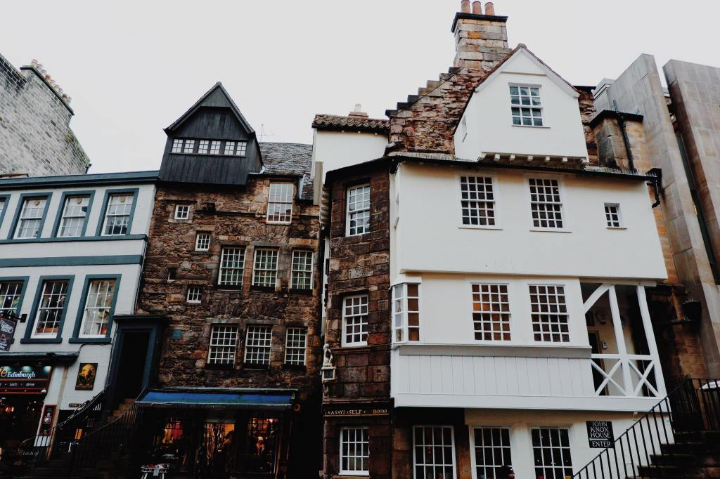 The quirky architecture of John Knox house. The building on the left is white with green windows In the middle is a brown building with small grid windows and black roof. On the right is the white facade of John Knox house with stairs leading up to the entrance.