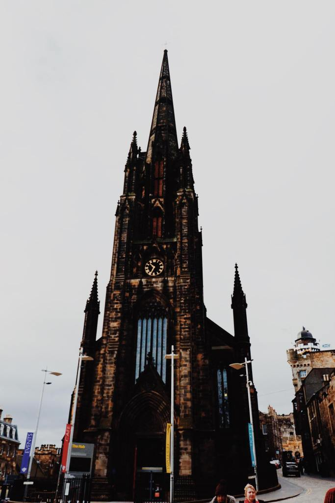 The gothic church, The Hub on The Royal Mile. The church is in the centre of the image and spans the entire length.  A clock and windows are centre of the Church.