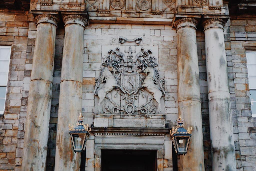 The Entrance to Holyrood Palace with the coat of arms above a door way. Two columns are either side of the door and two lampposts hang from the door.