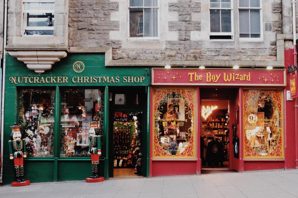 Storefronts on the Royal Mile. On the left is the Nutcracker Christmas Shop in green with two nutcrackers at the windows on the right is the Boy Wizard in red with Harry Potter march in the windows