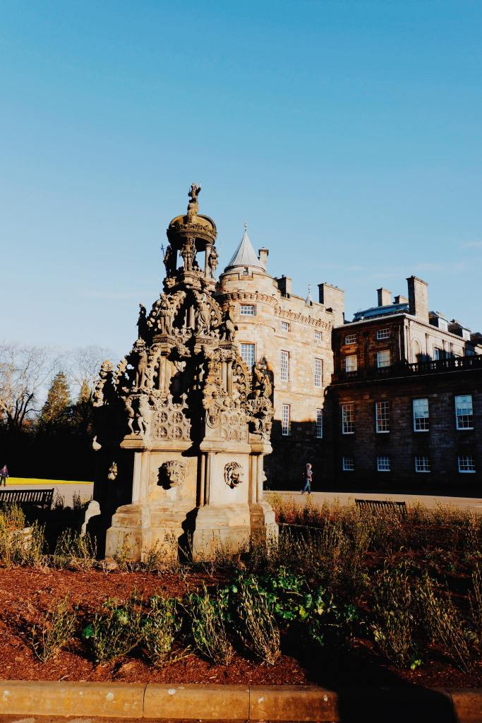 The Palace of Holyrood on the Royal Mile Edinburgh. At the front of the image is a fountain with the palace behind and blue skies.