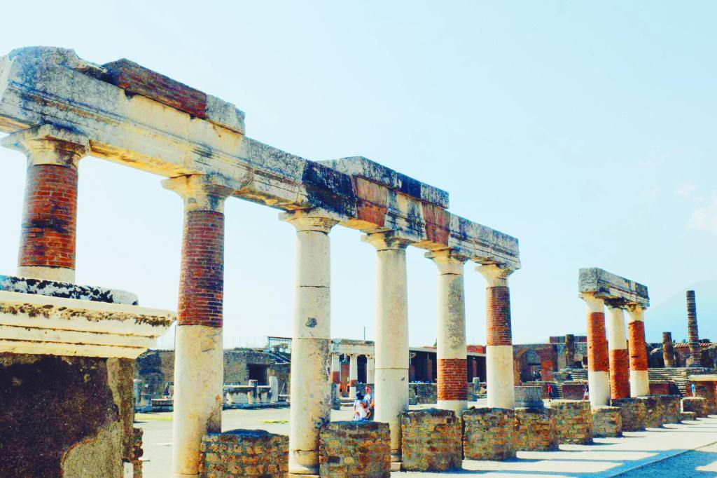 Columns in the forum at Pompeii. The columns are white and red brick and have 10 pillars with smaller brick pedestals beside.