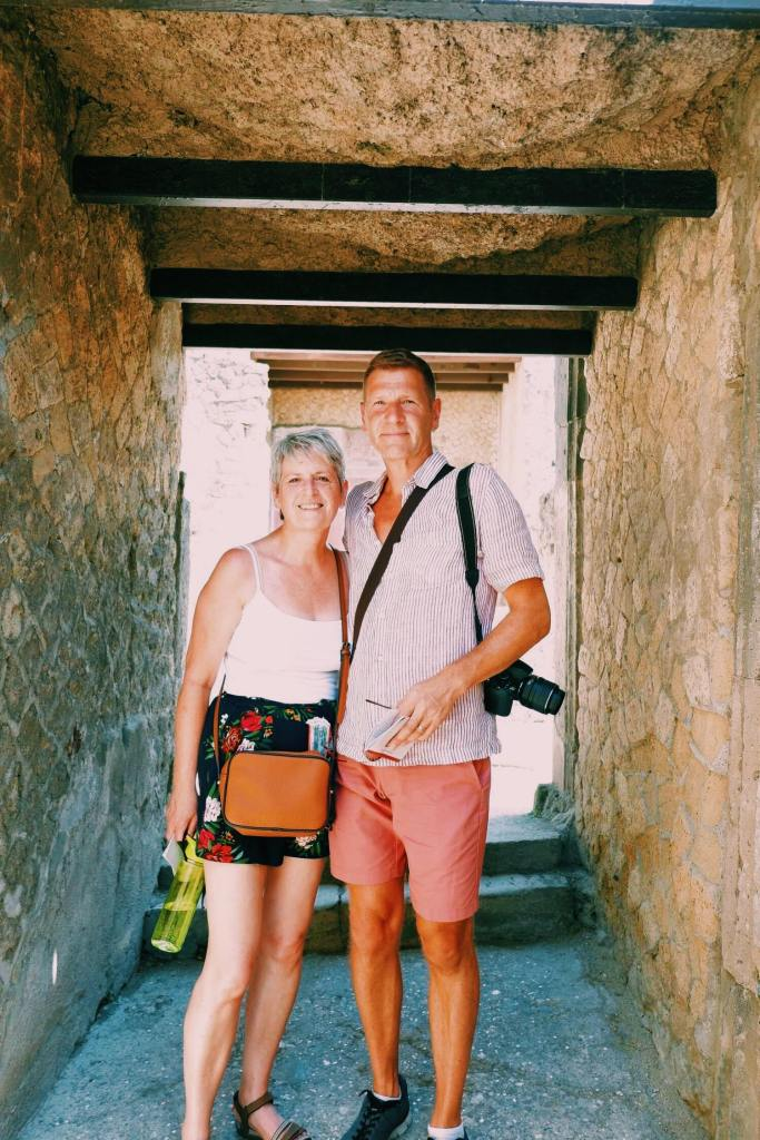 Mum and dad in a ruined house in Herculaneum. They stand with arm around each other. Both are wearing shorts carrying a water bottle and camera