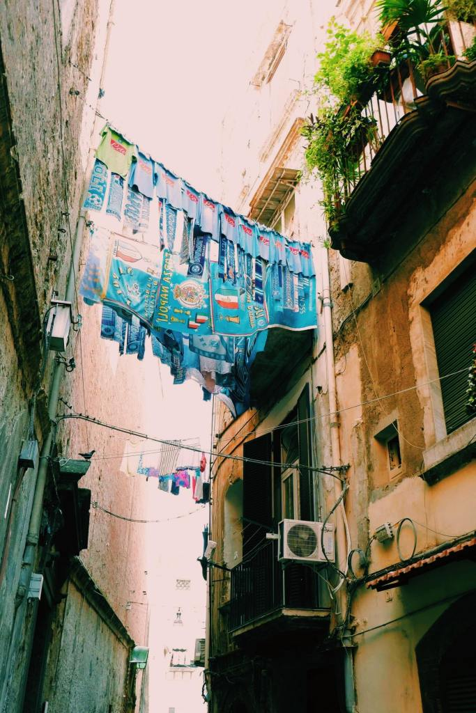 Street in the historic quarter of Naples Italy. Between the two buildings with balconies are washing lines with blue football towels and scarves and tshirts hanging