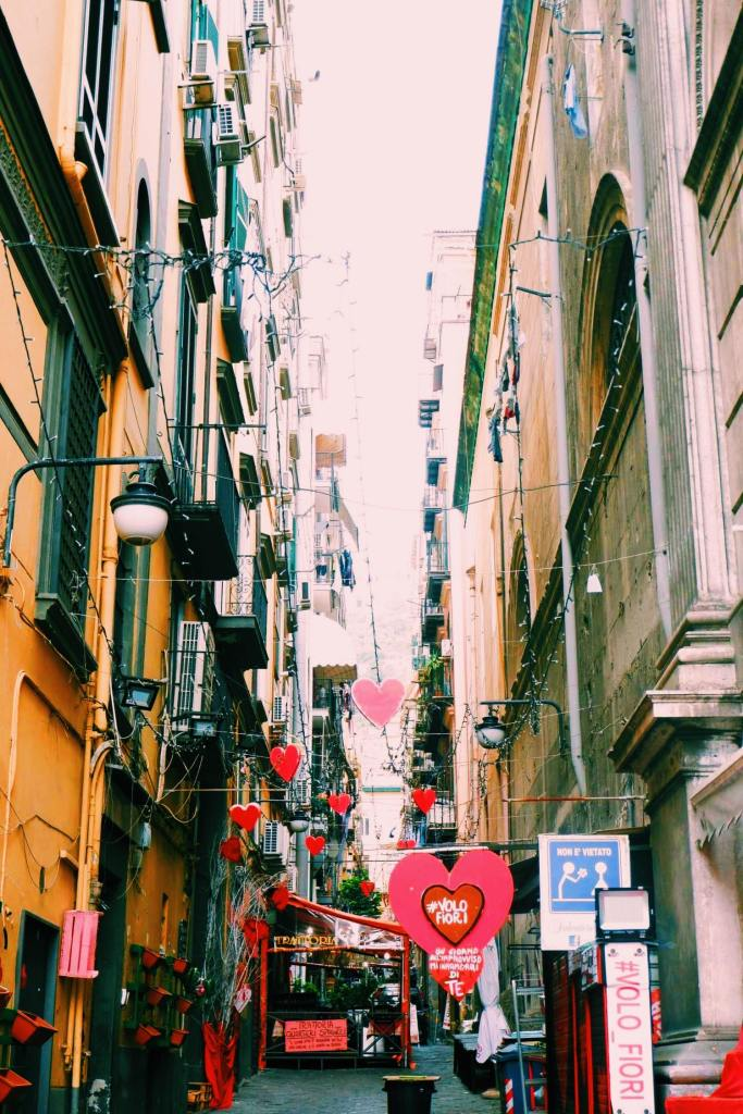 Street in the Spanish quarter of Naples. Between the buildings are red hearts with #volofiori