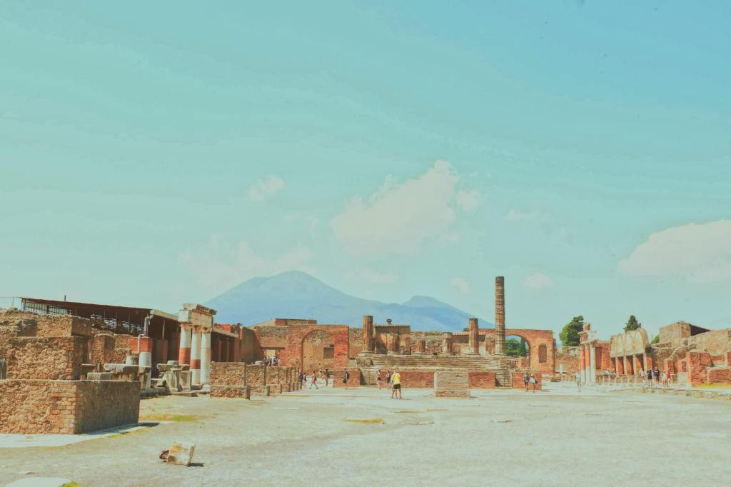 The forum at Pompeii in the Bay of Naples. The image shows the ruins and columns across the centre and Vesuvius in the background.