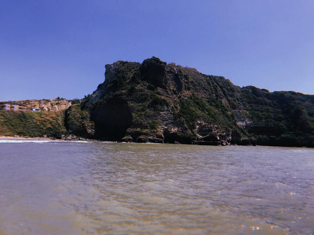 The beach at Torregaveta, at the front of the image is the sea and across the middle is large cliffs against a blue sky.