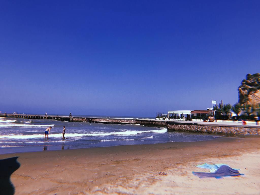 Beach at Torregaveta, sand and sea and a pier extending across the middle of the image
