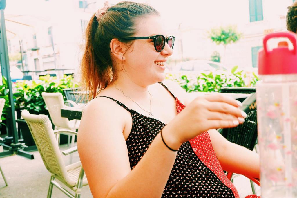 Image of Holly smiling at bar. she sits in profile with brown sunglasses and her hair in a pony tail. She wears a black and red dress and hand is raised.