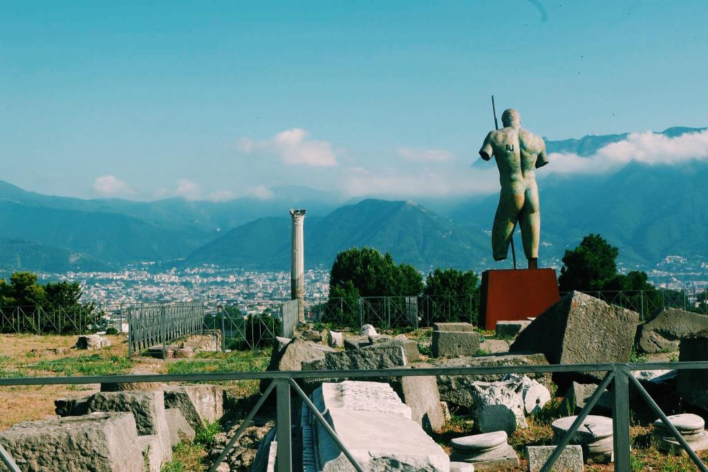 The exit of Pompeii with ruined blocks and a column. At the right is the back side of a nude bronze statue.