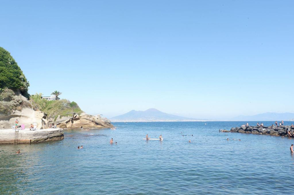 The beach at Pausilypon, Isola di Gaiola, Naples. The sea covers the lower half of the image with some cliffs and stone pier at either edge. At the horizon is Vesuvius