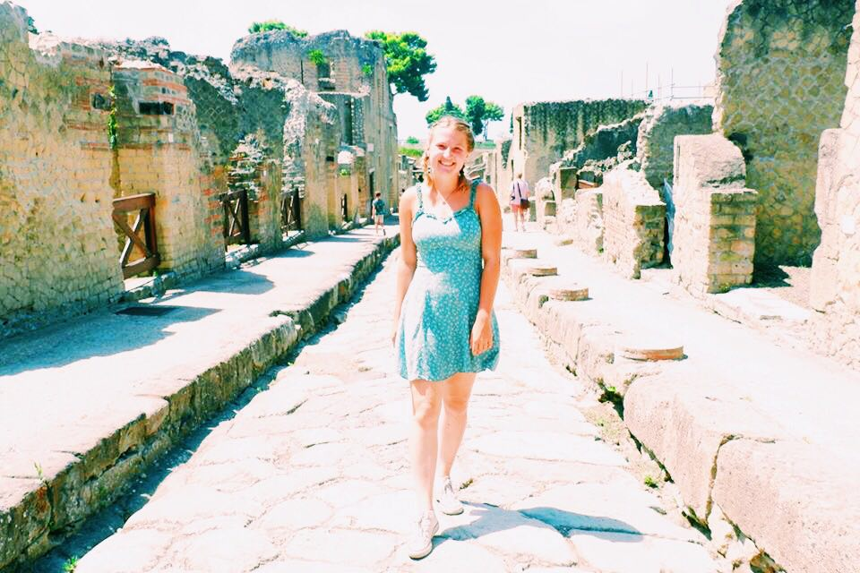 Emily standing in a green dress in the middle of a street in Herculaneum, Naples. Either side of the street are ruins of buildings.